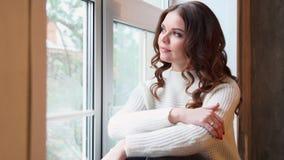 坐由窗口的年轻美丽的妇女在冬天 股票录像