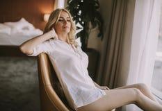 坐由窗口的白肤金发的妇女在天光 库存图片