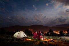 坐由篝火的浪漫对游人在多云天空下 免版税库存照片