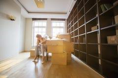 坐由纸板箱的全长被注重的妇女在新房里 图库摄影