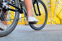 坐由自行车背面图的女孩的腿 免版税库存图片
