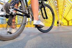 坐由自行车背面图的女孩的腿 免版税库存照片