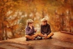坐由水和谈话的两个男孩 库存图片