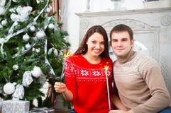 坐由Cristmas树的年轻夫妇 免版税库存图片