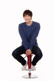 坐的可爱的亚裔年轻人 免版税图库摄影