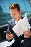 坐的商人户外读报纸和使用电话 图库摄影