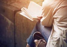 坐的女孩读古典文学 免版税库存图片