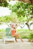 坐的女孩sunbed在树附近 图库摄影