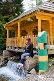 坐的妇女享用俏丽的瀑布 免版税图库摄影