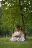 坐的小女孩下 免版税库存照片