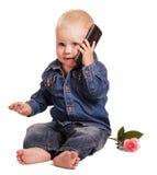 坐的小男孩拿着手机在耳朵附近,起来了 库存图片