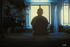坐的患者图在医院病床在背景  免版税库存图片