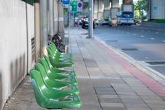 坐的椅子等待的公共汽车位于公共汽车站 免版税库存图片