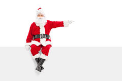 坐盘区和指向与手指的圣诞老人 免版税库存照片
