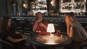 坐直在酒吧关闭的小桌上的晚礼服的三个年轻女朋友 女孩一起有庆祝 影视素材