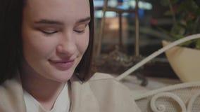 坐直在餐馆关闭的一俏丽的年轻女人的接近的画象 查寻的夫人的面孔下来和 股票视频