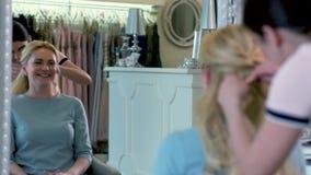 坐相对于镜子的愉快的白肤金发的妇女在美容院 做发型的美发师 股票视频