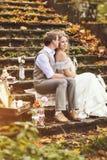 坐石步和拥抱在秋天森林里的减速火箭的样式婚礼夫妇,包围由美丽的装饰 库存图片