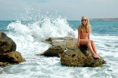 坐石头和飞溅在海的美丽的妇女 库存图片