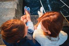 坐码头近对海和看彼此,旅行概念的年轻夫妇上面接近的视图  免版税库存照片