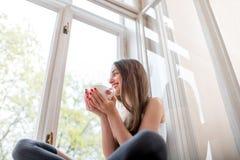 坐窗台和看Th的年轻和逗人喜爱的夫人 免版税库存图片