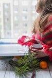 坐窗台和读书的一件被编织的毛线衣的一个小女孩 图库摄影