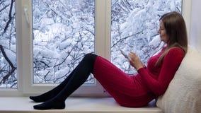 坐窗台,看窗口和使用有耳机的红色礼服的俏丽的女孩片剂计算机 外部冬天 股票视频