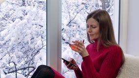 坐窗台,饮用的茶和使用智能手机的红色礼服的俏丽的女孩 外部冬天 股票录像
