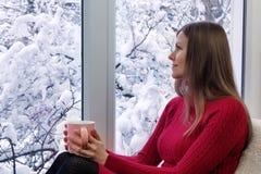 坐窗台,饮用的茶和看窗口的美丽的女孩 外部冬天 免版税库存图片