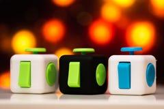 坐立不安立方体反重音玩具 手指戏剧玩具细节使用为放松 在五颜六色的bokeh背景安置的小配件 免版税库存照片