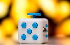 坐立不安立方体反重音玩具 手指戏剧玩具细节使用为放松 在五颜六色的bokeh背景安置的小配件 库存照片