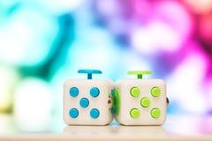 坐立不安立方体反重音玩具 手指戏剧玩具细节使用为放松 在五颜六色的bokeh背景安置的小配件 免版税图库摄影
