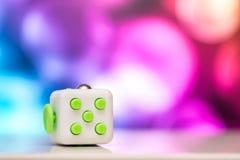 坐立不安立方体反重音玩具 手指戏剧玩具细节使用为放松 在五颜六色的bokeh背景安置的小配件 库存图片