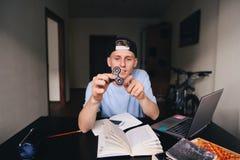 坐立不安锭床工人在坐在他的屋子里的一个年轻人的手上在书桌 在旋转的焦点 免版税库存照片