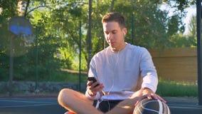 坐篮球场和键入在电话的英俊的愉快的年轻人,对球和听的音乐负,微笑 股票录像