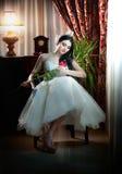 坐美丽的新娘拿着在经典风景的一朵红色玫瑰 免版税图库摄影