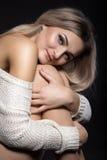 坐美丽的年轻白肤金发的妇女画象拥抱她的kne 免版税库存图片
