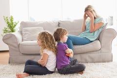 坐胳膊的恼怒的兄弟姐妹横渡了与沙发的翻倒母亲 免版税库存照片
