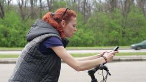 坐自行车和发短信在智能手机的女孩 影视素材