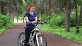 坐自行车和发短信在智能手机的女孩 股票录像