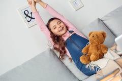 坐舒展的小女孩在家递微笑愉快 免版税库存图片