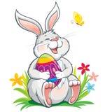 坐草和拿着被绘的复活节彩蛋的可爱的兔宝宝 图库摄影