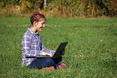坐草和演奏膝上型计算机的小女孩 免版税库存图片