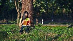 坐草和读一本书的妇女在庭院里 影视素材