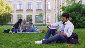 坐草和读有趣的书的愉快的两种人种的男学生 免版税库存照片