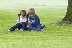 坐草在公园和使用片剂个人计算机的小男孩 技术,生活方式,教育,人概念 免版税库存照片