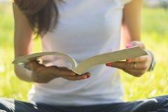坐草甸和拿着一本开放书的少妇 免版税库存照片