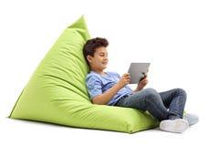 坐装豆子小布袋和看片剂的快乐的小男孩 库存图片