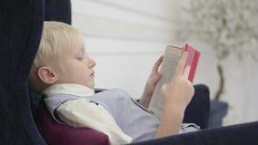 坐读一本厚实的书的一个严肃的白肤金发的男孩在椅子 股票录像