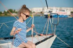 坐豪华消遣小船的太阳镜的逗人喜爱的矮小的健康孩子 免版税库存照片